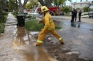 Firefighters work to fix a leak in the water infrastructure beneath the pavement outside a home in Los Angeles, California, U.S., March 22, 2017.  REUTERS/Lucy Nicholson - RC12520EEAE0